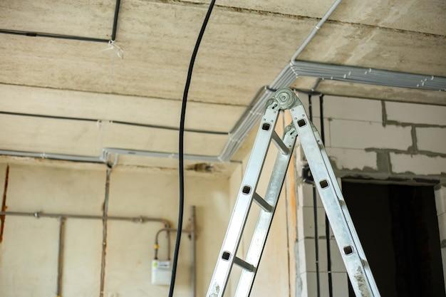 Escalera de aluminio y cables eléctricos tendidos en corrugado protector instalados en techo y pared en una sala en obras.