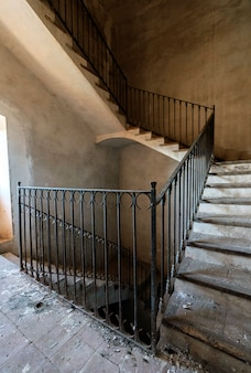Escalera antigua con barandilla metálica.