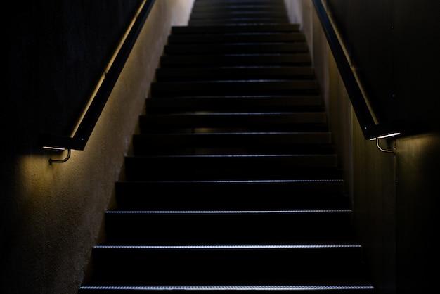 Escalera con barandilla iluminada en la oscuridad.