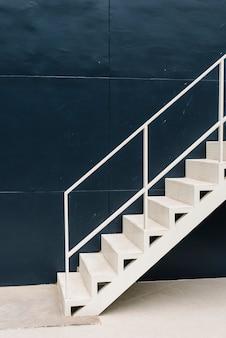 Escalera blanca en un edificio azul.