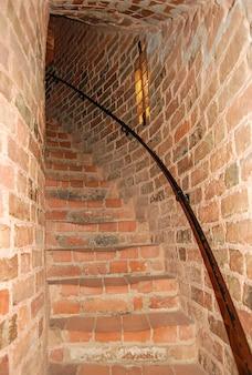 Escalera de caracol en un castillo de ladrillo rojo.