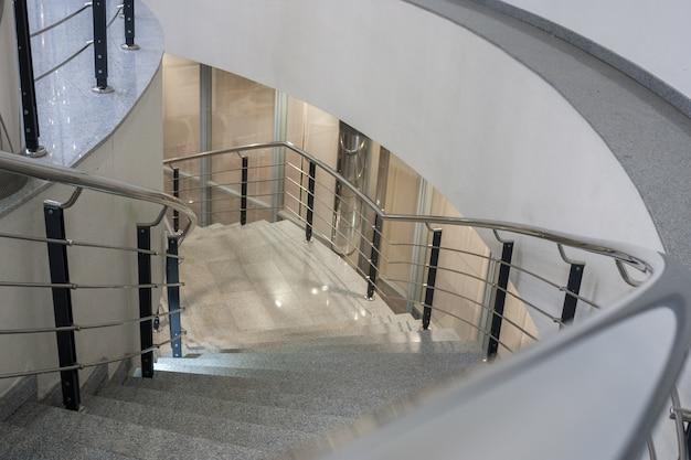 Escalera de caracol de piedra iluminada con barandilla de metal.