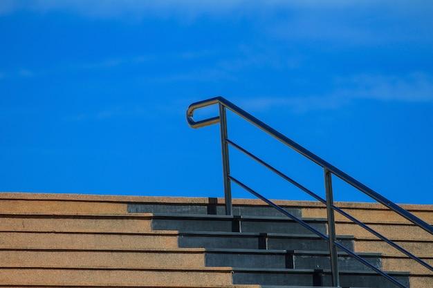 Escalera de cemento en el parque con barandilla de acero.