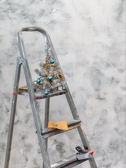 Escalera de construcción con un pequeño árbol de navidad se encuentra en la pared pintada. concepto de reparaciones inacabadas a tiempo.