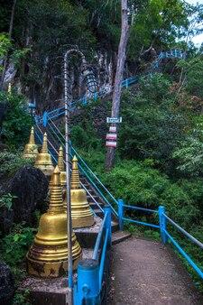 Escalera empinada de hormigón a la roca y estupas budistas doradas cercanas. la linterna está envuelta en alambre de púas de monos. muchos árboles verdes.