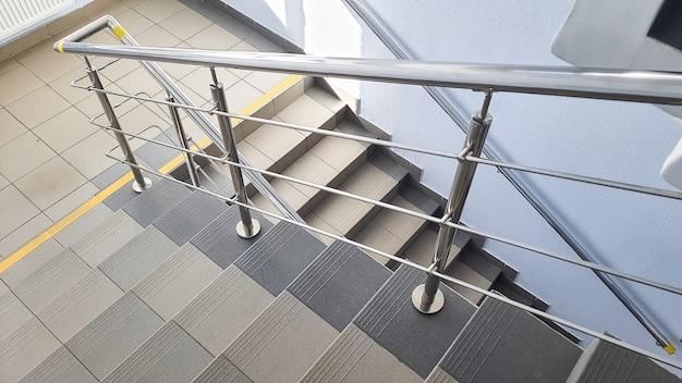 Escalera a la entrada de un edificio de varios pisos. pasos de escaleras en la escalera. escaleras dentro del edificio. escalera en un edificio moderno. escalera vacía en un edificio tranquilo.