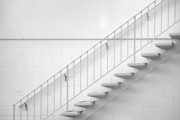 Escalera, escaleras de hormigón con barandilla de metal en la pared de ladrillo blanco, arquitectura minimalista