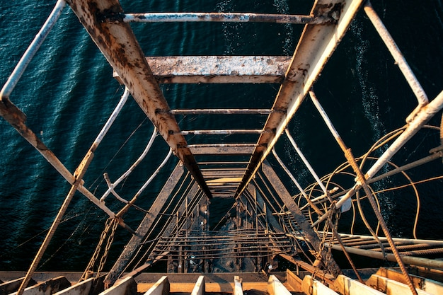 Escalera extremadamente vieja y desgarrada que baja al mar ondulado a partir de un viejo puente