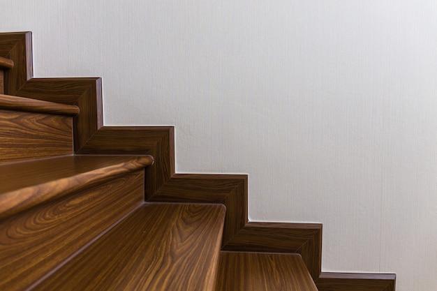 Escalera hecha a medida interior de la casa con escalera de madera y paredes blancas.