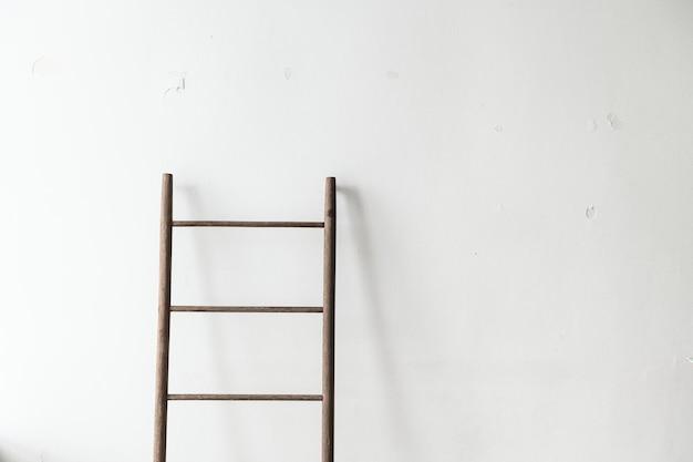 Escalera de madera apoyada contra una pared.