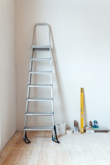 Una escalera de mano con herramientas de pintura en una habitación de una casa o apartamento