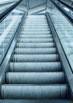 Escalera mecánica en el aeropuerto de francia con panel terminal