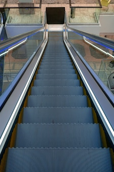 Una escalera mecánica vacía dentro de un moderno centro comercial conduce hacia abajo. el concepto de clientes que se trasladan de centros comerciales a internet.