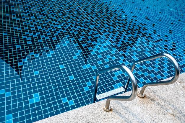 Escalera metálica de acero inoxidable en la piscina azul de verano