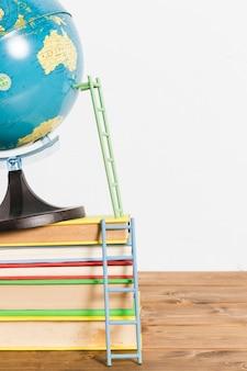 Escalera de papel en el mapa global terrestre soporte bola y libros sobre mesa de madera