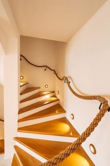 Escalera con peldaños iluminados y barandas de cuerda en una casa con paredes blancas