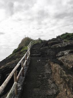 Escalera de piedra hacia la cima de la colina con barandilla de madera bajo cielo nublado gris después de la lluvia