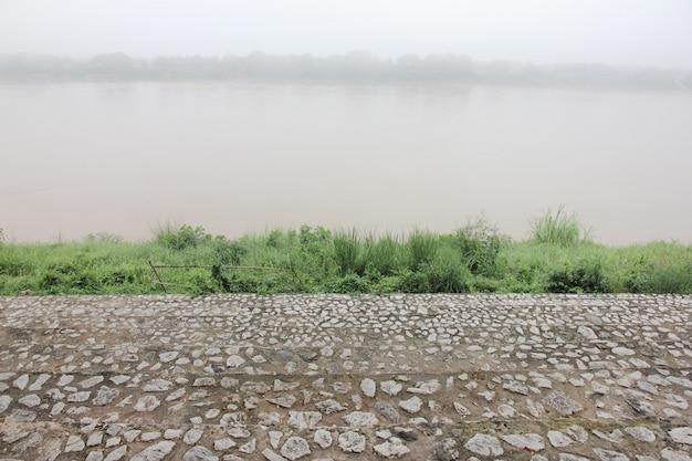 Escalera de piedra en ribera cubierta por neblina.
