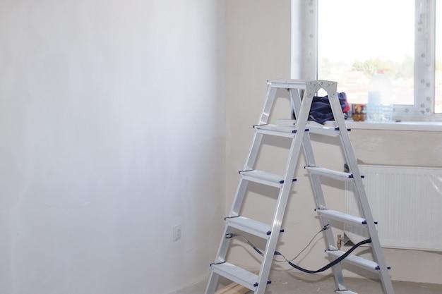 Escalera plegable de aluminio en una habitación con pared y ventana enlucidas en blanco. reforma de vivienda en casa nueva. copie el espacio.