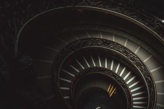 Escalera redonda en un museo del vaticano que lleva a los visitantes a mirar obras de arte cristianas