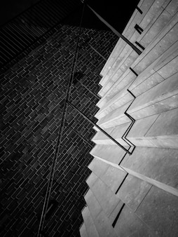 Escaleras con barandilla y pared de ladrillo.