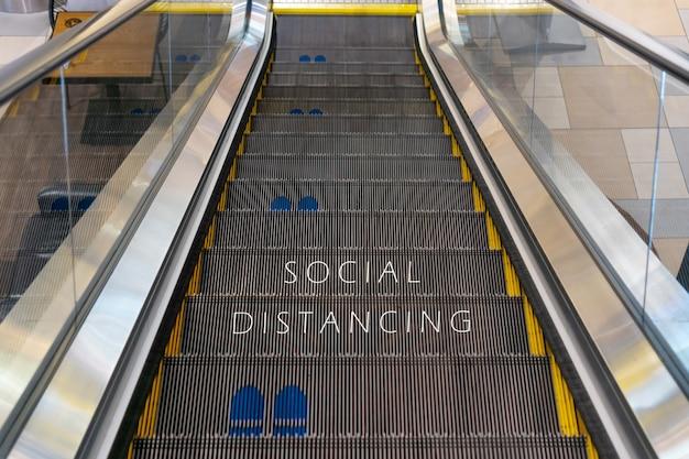 Escaleras mecánicas con símbolo de huella para distanciamiento social durante el coronavirus