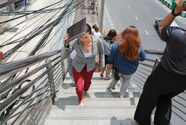 Escaleras del paso superior de la mujer de negocios que caminan en el día soleado.