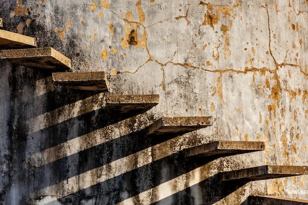 Escaleras proyectando sombra sobre la antigua muralla desgastada
