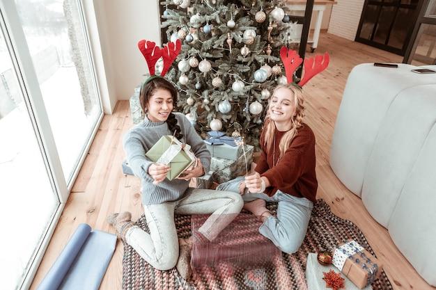 Escalofriante cerca del árbol. atractivas chicas divertidas que se preparan para la temporada navideña mientras llevan cajas y bengalas