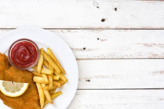 Escalope vienés con patatas fritas en madera