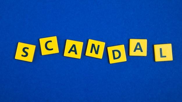 Escándalo palabra escrita en estilo combado.