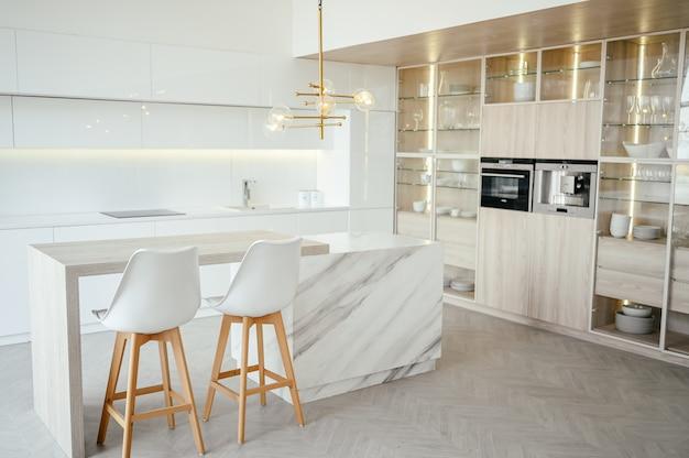 Escandinava cocina clásica de lujo moderna y vacía con detalles de madera, blanco y mármol, muebles nuevos y elegantes, diseño interior nórdico minimalista. taburetes de bar, expositor de vidrio, vajilla y cristalería.