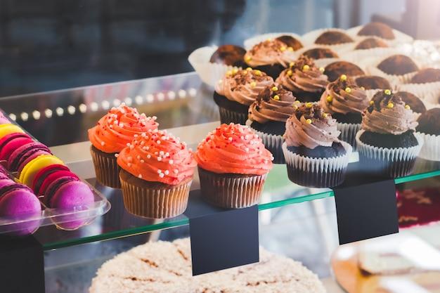 Escaparate con dulces en la cafetería. magdalenas y macarrones de colores en la exhibición de la torta
