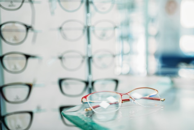 Escaparate de gafas en primer plano de la tienda óptica, nadie. protección para los ojos, anteojos en el estante de la tienda óptica, elección de anteojos