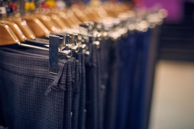 Escaparate con pantalones de hombre en perchas en una tienda de hombres