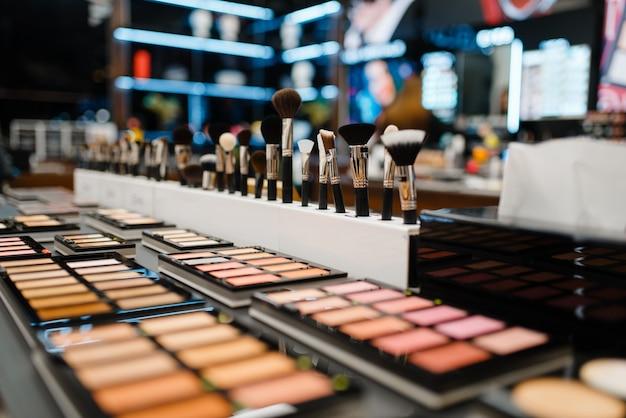 Escaparate con polvos y sombras en la tienda de cosméticos, nadie. salón de belleza de lujo, estante con productos en el mercado de la moda.