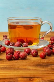 Escaramujos. una taza de té de rosa mosqueta en una mesa de madera. vertical. copie el espacio.