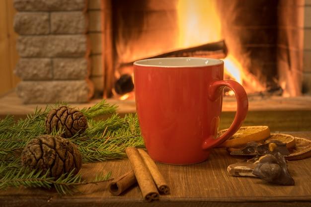 Escena acogedora junto a la chimenea con taza de bebida caliente, tangarine, conos y canela.