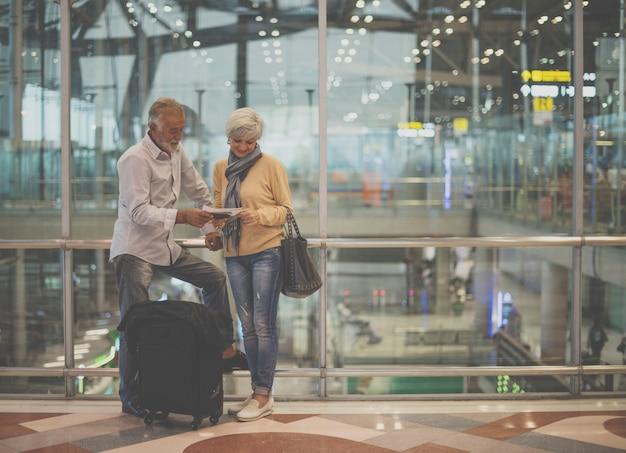 Escena del aeropuerto de pareja senior viajando