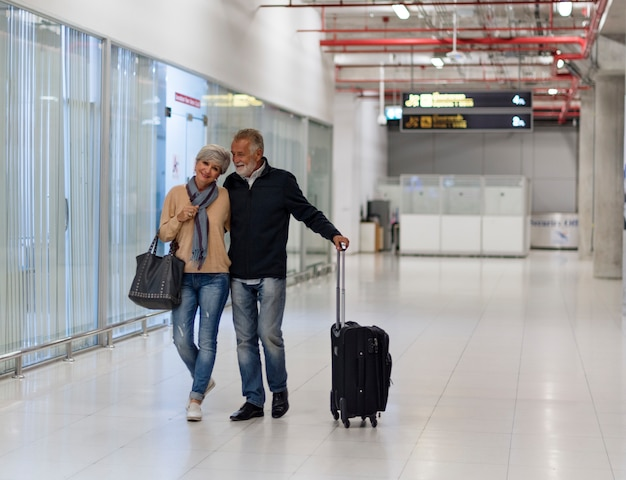 Escena de aeropuerto viajando pareja senior