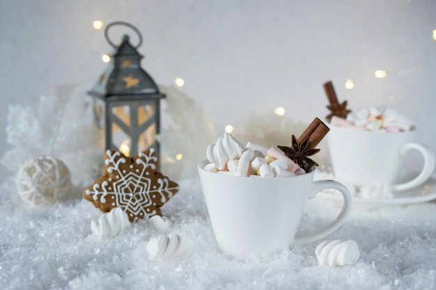 Escena borrosa helada de invierno y bebida de especias de chocolate de navidad con galletas en tazas blancas