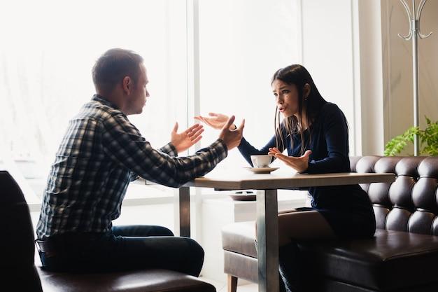 Escena en café - conflicto de pareja discutiendo durante el almuerzo.