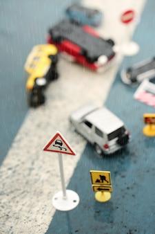 Escena de coches en miniatura, accidente de modelo de juguete en un día lluvioso, señal de tráfico resbaladizo.