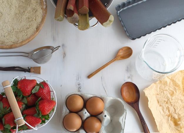 Escena de cocina, utensilios de cocina e ingredientes para pastel, vista superior