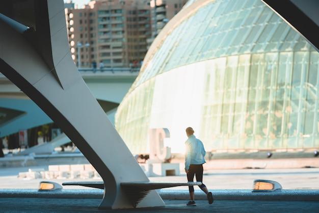 Escena de deportista caminando por la ciudad entre edificios al atardecer