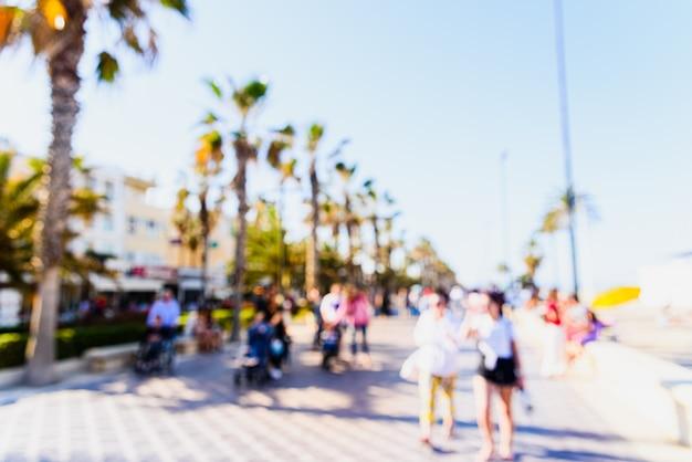 Escena desenfocada para usar como fondo de un paseo marítimo con palmeras y turistas de vacaciones.
