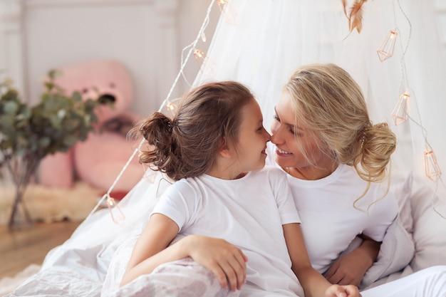 Escena familiar. feliz madre e hija en una cama