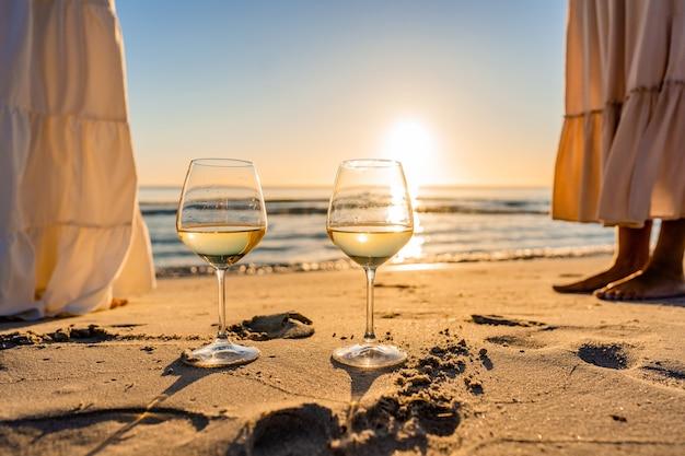 Escena de fiesta en la playa al atardecer o al amanecer con dos chicas boho multirraciales irreconocibles