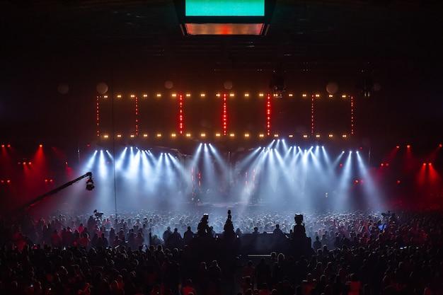 Escena iluminada por hermosos rayos de equipos de iluminación. la multitud del concierto se divierte en el centro de la gran sala.