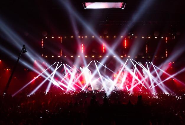 Escena iluminada por hermosos rayos de equipos de iluminación. la multitud del concierto divirtiéndose en el centro de la gran sala. la televisión se transmite en vivo. mucha gente mira hacia el escenario.